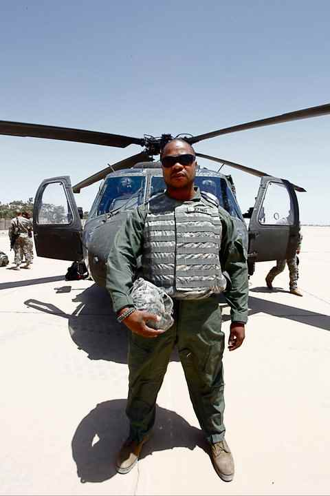 Xzibit standing in front of a Black Hawk in Iraq